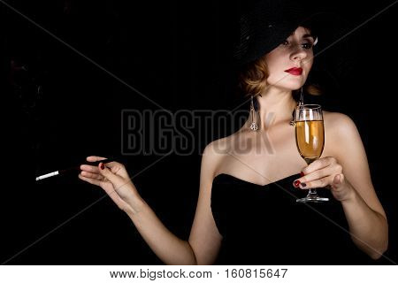 Beauty retro female model with professional makeup holding mouthpiece and glass of champagne. fashion vintage woman on a dark background.