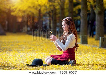 Beautiful Girl with Yellow Leaves in Nami Island Korea. Nami island in autumn.