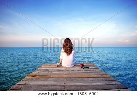 Girl sitting alone on a the wooden bridge on the sea. (frustrated depression)