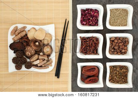 Chinese alternative herbal medicine selection with herb selection in china dishes on a bamboo mat with chopsticks and on marble background.