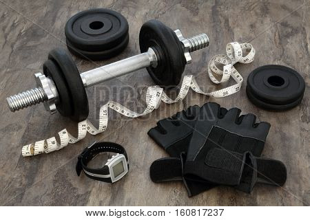 Weight training equipment for body builders with dumbbell weights, heart rate monitor watch, leather gloves,  and tape measure over marble background.