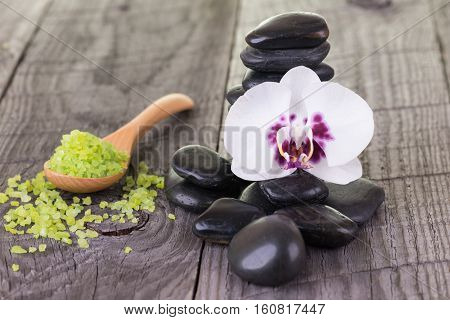 Spa with bath salt, orchid and black stones on wooden background