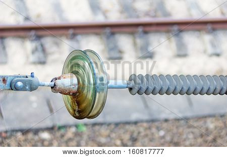 High-voltage ceramic insulator on railway tracks background