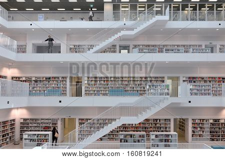 Stuttgart, Germany - April 16, 2015: Interior of modern library in Stuttgart. White floors with bookshelves connected with stairs.