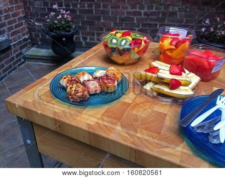 Fresh Fruit Brunch breakfast on wood chopping board outdoors with pastry breads banana, kiwi, melon, strawberry, outdoor patio picnic style on brick patio with flowers and room for copy space or writing