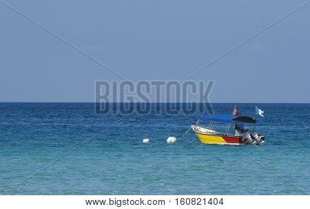 Boat at crystal clear waters Perhentian Kecil Island beach Terengganu Malaysia.