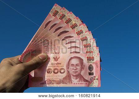 Asian men left hand hold few hundred banknotes of Thailand on the sky background (Thai baht)