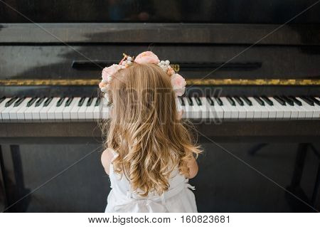 Piano school for little girl. Education. Black piano.