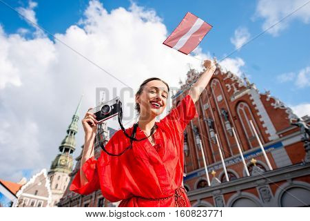 Portrait of a young female tourist with latvian flag on the main old town square in Riga. Woman having great vacations in Latvia