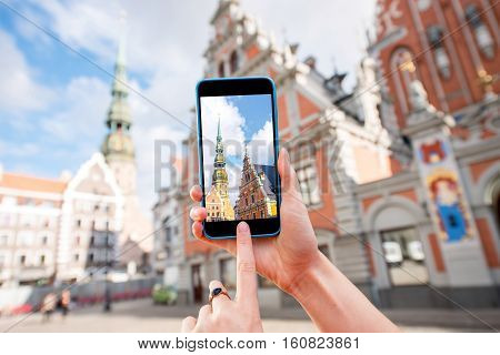 Photographing with smart phone famous houses of Blackheads and Peter church in the old town's center in Riga