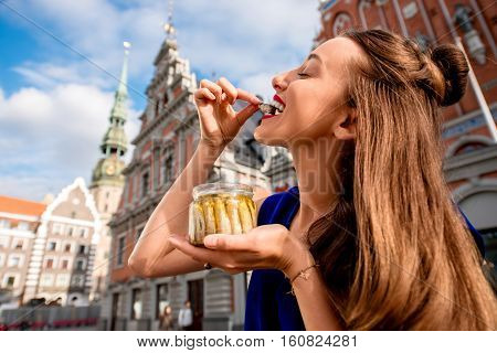 Young woman eating Riga's sprats in the old town square in Latvia. Riga is famous for it's tasty golden and smoked fish called sprats.