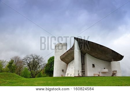 RONCHAMP, FRANCE - APRIL 23, 2016: Pilgrimage Church of Notre Dame du Haut in Ronchamp in the Vosges mountains. Facade on the background of mountain scenery. The architect is Le Corbusier. Franche-Comte, France.