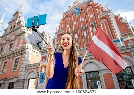 Young female tourist making selfie portrait with latvian flag on the old town square in Riga. Woman having great vacations in Latvia
