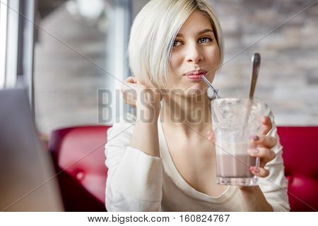 Portrait of beautiful young woman drinking hot chocolate in cafe