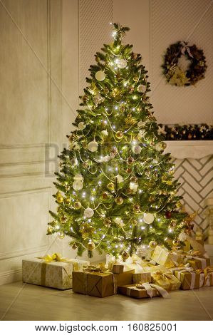 Elegant Christmas tree decorated with glistening glass balls a beads and fairy lights. Under a fir-tree the mountain of Christmas gifts in beautiful packings. The room is festively decorated.