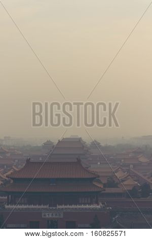 vertical shot of the Forbidden City in Beijing China on a foggy day.