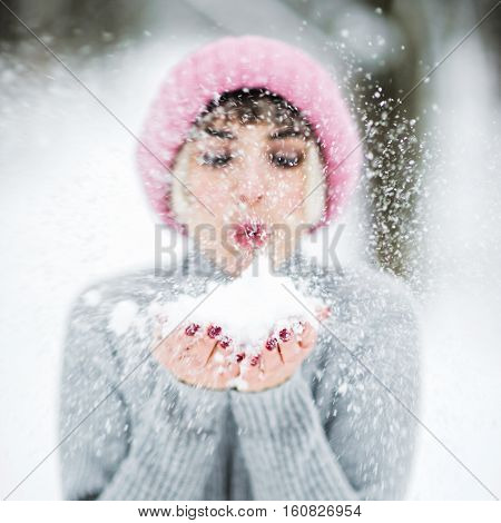 Portrait of a beautiful young woman in pink hat in winter forest