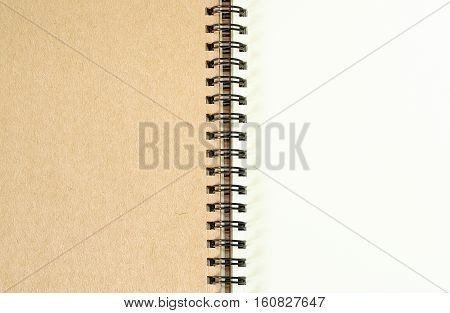 Open blank spiral note book  brown and white background.