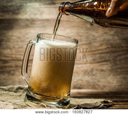 Foamy beer from bottle filled into mug standing on empty wooden background