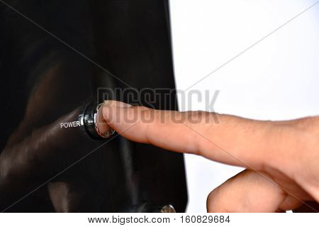 The person's finger will going to push on the power button on white back ground.
