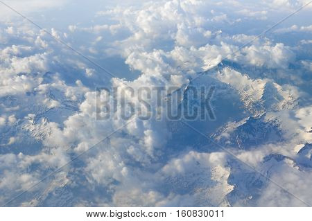 Sky scenery. Aerial view over the cumulus clouds and mountain peaks covered with snow on a sunny day. Swiss Alps.