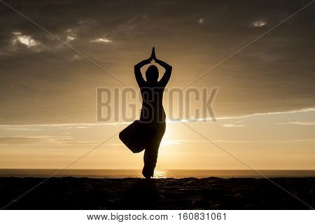 A silhouette of woman on a tree asana yoga pose on the beach.