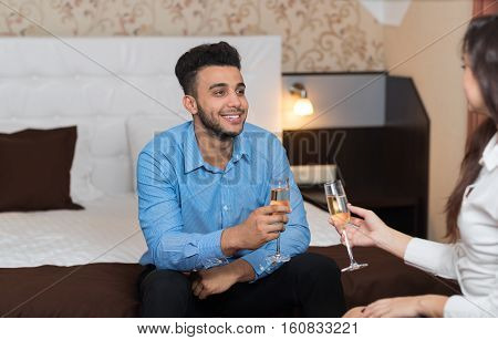 Latin Businessman Sitting on Bed In Room With Businesswoman Drink Champange Business Man And Woman Arriving To Hotel