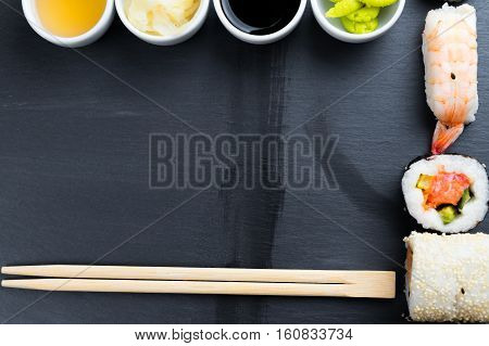 Japanese sushi with chopsticks on black kitchen slate plate. Typical asian cuisine. Maki and nigiri. Soy and fish sauce ginger and japanese horseradish wasabi in small white bowls. Copy space in center.