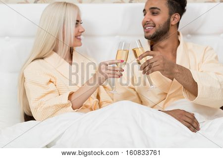 Young Couple Hold Glass Of Champagne Sitting Bed, Happy Smile Man And Woman Honeymoon Lovers In Bedroom
