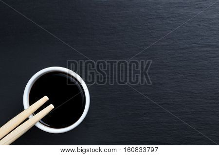 Soy sauce in small white bowl with chopsticks on black kitchen slate plate. Typical asian cuisine spice. Copy space on the right.