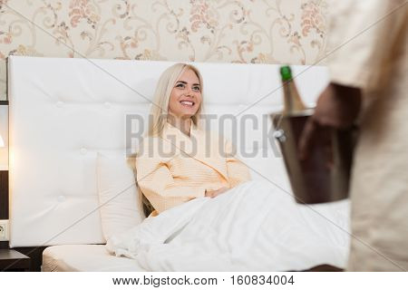 Man Hold Ice Bucket With Champange, Smiling Woman In Bed Young Couple Hotel Lovers In Bedroom