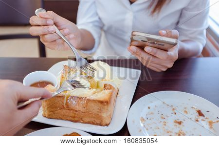 Asian woman are eating ice ream and delicious bread.Focus on fork