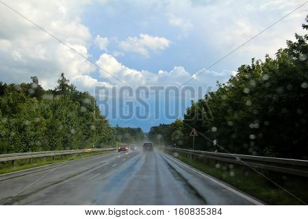 Wet road / The car rides on a wet motorway.