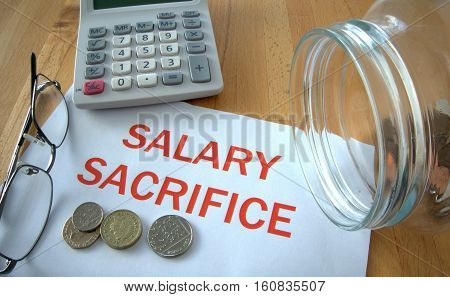 Salary sacrifice with coins on paper and in pot and calculator behind