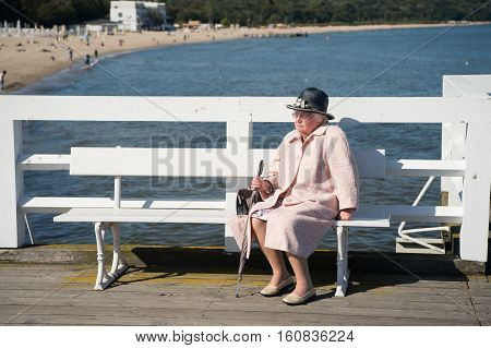 Sopot Poland - September 19 2016: elegant senior woman or old lady sits on wooden bench on sea pier or dock for pleasure and promenade on sunny day on seascape background
