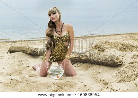 Young Blonde With A Goldfish In An Aquarium