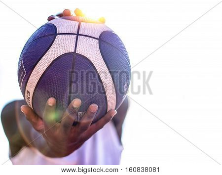 Young American basketball player holding in his hands a blue and white basket ball against white in the background - Concept about people and sport