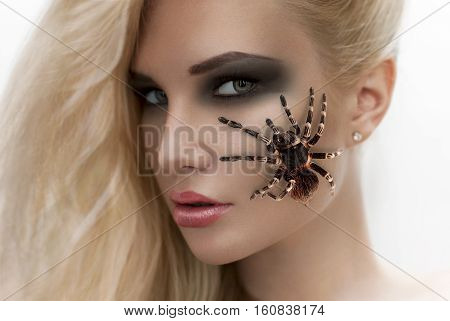 portrait of beautiful asian girl with spider on the cheek
