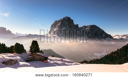 wood cottage in the dolomiti in a sunny winter day