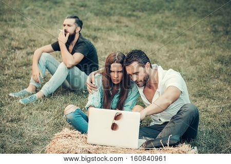 Young people or friends relax handsome man smokes while love couple of pretty girl girlfriend and boyfriend watch laptop computer on natural background