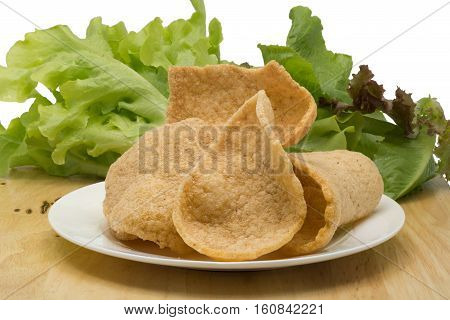 Prawn cracker and vegetables in a white plate on a wooden board on white background