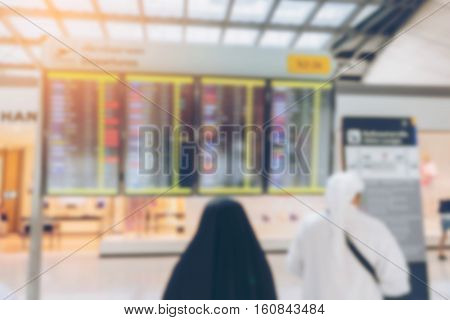 Blurred Arabic Businessman Passenger Looking At Timetable Board At The Airport