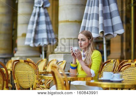 Young Romantic Parisian Girl In An Outdoor Cafe Using Tablet