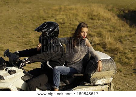 Handsome man and pretty girl ride quad bike on field road on natural background