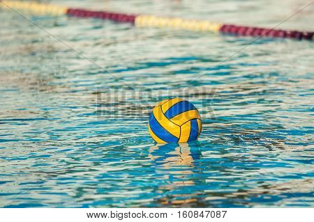 Floating water polo game ball buoyant in swimming pool.