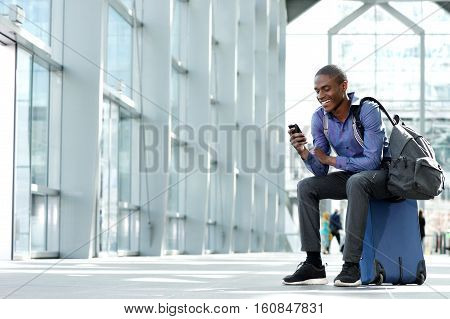 Smiling Young Businessman Sitting On Suitcase Looking At Phone