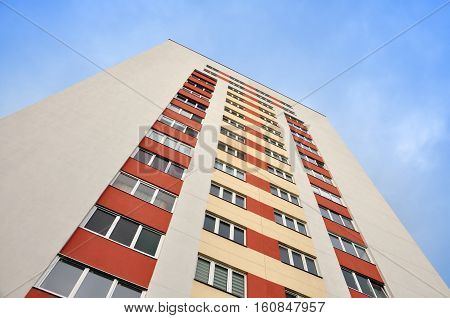 Grodno, Belarus - November 4, 2016: White facade of a modern multistory highrise residential building with red yellow inserts. Look up.