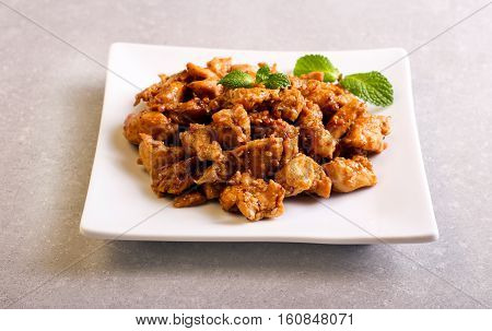 Spicy chicken breast with sesame on plate top view
