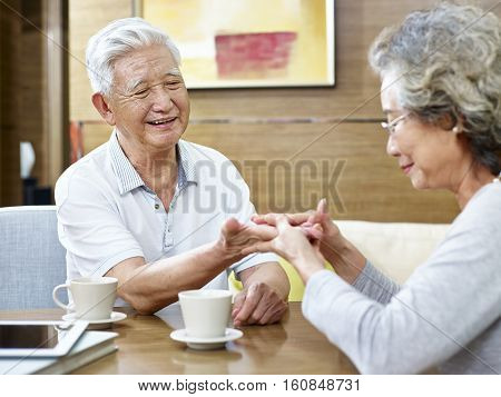 senior asian woman trying to read the palmistry of her husband while having coffee together.