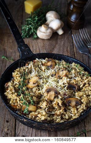 Risotto with mushrooms served in iron skillet on wooden table. Close up view, rustic style